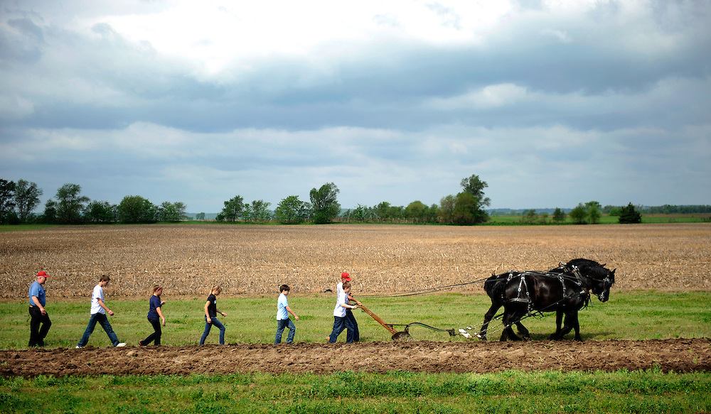 Volunteers lead school children along a furrow dug by a plow pulled behind Percheron draft horses Thursday at Three Sisters Park in Chillicothe. Farming methods circa 1918 were demonstrated for the several hundred tri-county area children including shucking corn that was then tossed into wagons pulled by mules, hand-planting techniques and corn gringing.