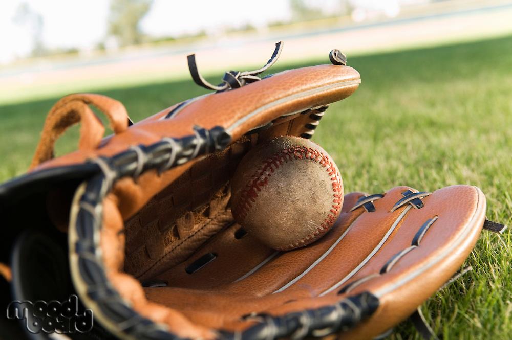 Baseball glove and ball on field (close-up)