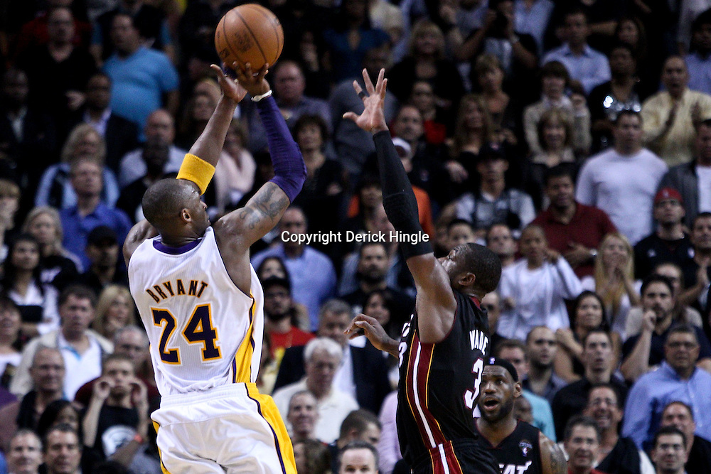 March 10, 2011; Miami, FL, USA; Los Angeles Lakers shooting guard Kobe Bryant (24) attempts a shot over Miami Heat shooting guard Dwyane Wade (3) during the fourth quarter at the American Airlines Arena. The Heat defeated the Lakers 94-88.   Mandatory Credit: Derick E. Hingle