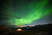 Northern Lights over backcountry campers in Stone Mountain Provincial Park, Northern Rockies, British Columbia