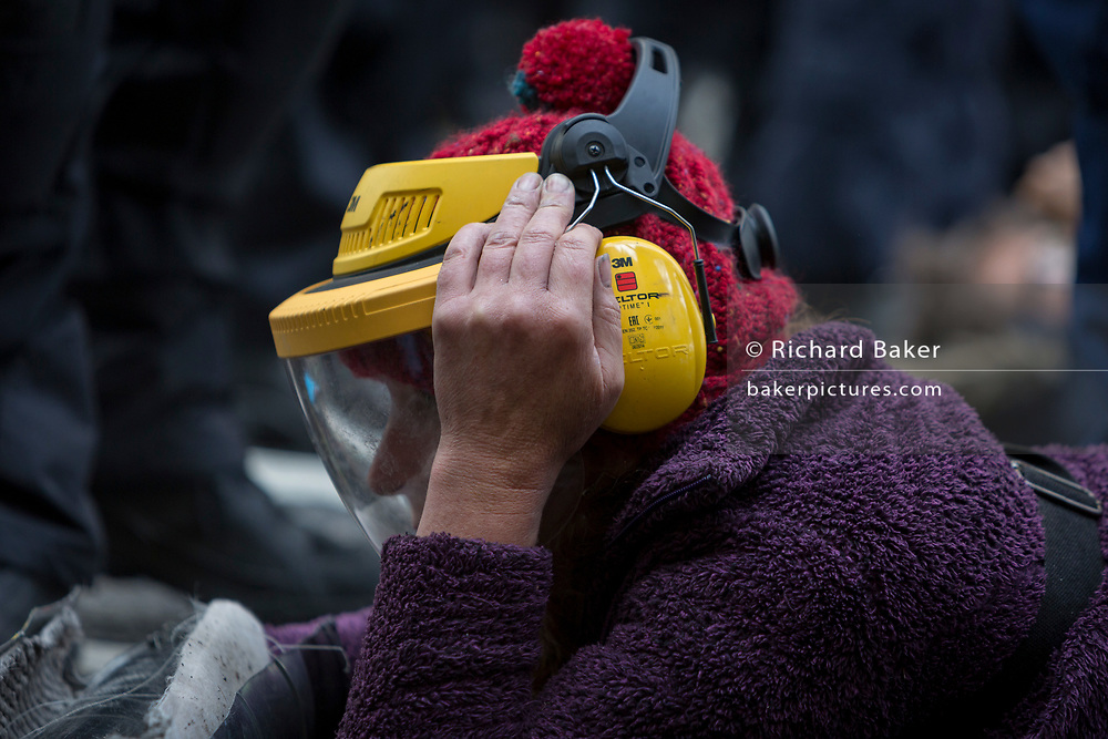 An environmental protester wears a protective helmet issued by police before a grinder is used to saw through chains on the road in Fleet Street on the 11th and final day of protests, road-blockages and arrests across London by the climate change campaign Extinction Rebellion, on 25th April 2019, in London, England.