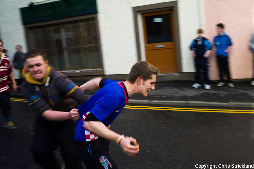 A ba' carrier is tackled by an opponent on the Canongate.