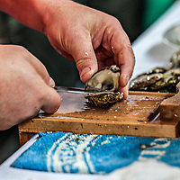 Closeup on chefs hands as he shucks oysters.