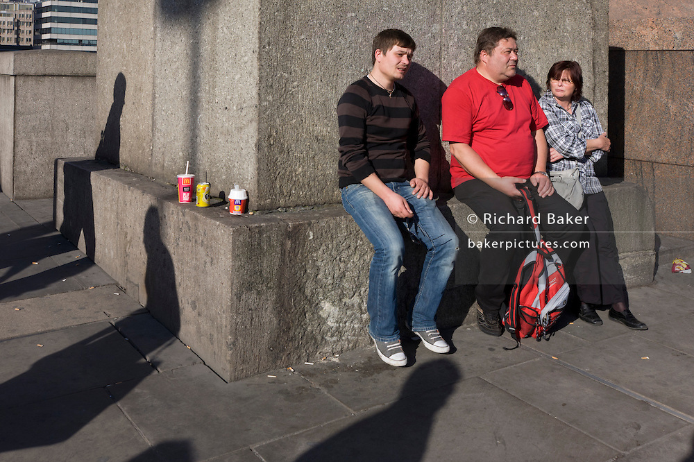 With three drinks cartons sit propped up on a stone ledge, three tourists rest around its corner, surrounded by the shadows of three commuters.