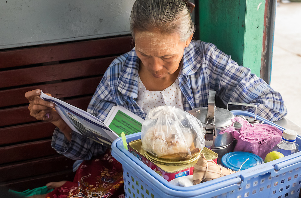 YANGON, MYANMAR - CIRCA DECEMBER 2013: Old Burmese woman reading a newspaper while awaits train to depart from Yangon Central Railway Station