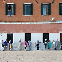 People wait for the water bus while resting against the wall in the shade  on the day the Italian Government and Heath Ministry has issued several warning for the current heath wave