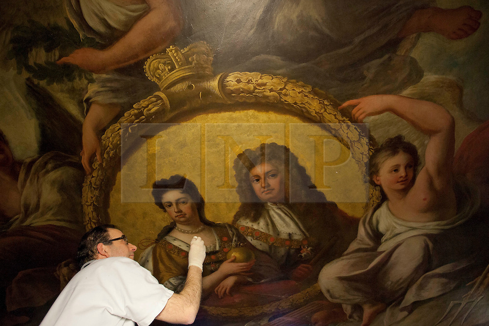 """© Licensed to London News Pictures. 04/03/2013. London, UK. On top of a scaffolding tower at around 40 feet in the air, restoration expert Francesco Rosellini works on gold leaf forming part of a portrait of Queen Anne and her consort Prince George, during restoration work to the ceiling of the 'Painted Hall' at Greenwich Old Naval College in London today (04/03/2013). The conservation work, paid for by the Heritage Lottery Fund (HLF), is the 10th time the Painted Hall (often described as """"finest dining hall in Europe"""") will have been restored since its completion in 1784 and will have taken around five months to complete when the hall is unveiled to the public in May of this year. Photo credit: Matt Cetti-Roberts/LNP"""