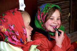 After school and behind the shop next to the school building a couple of girls giggly apply lipstick with great concentration.