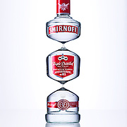 Triple Distilled Smirnoff vodka beauty bottle against a white glossy background Ray Massey is an established, award winning, UK professional  photographer, shooting creative advertising and editorial images from his stunning studio in a converted church in Camden Town, London NW1. Ray Massey specialises in drinks and liquids, still life and hands, product, gymnastics, special effects (sfx) and location photography. He is particularly known for dynamic high speed action shots of pours, bubbles, splashes and explosions in beers, champagnes, sodas, cocktails and beverages of all descriptions, as well as perfumes, paint, ink, water – even ice! Ray Massey works throughout the world with advertising agencies, designers, design groups, PR companies and directly with clients. He regularly manages the entire creative process, including post-production composition, manipulation and retouching, working with his team of retouchers to produce final images ready for publication.