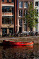 Amsterdam, Holland. Red boat moored to the side of the canal.