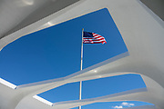 As a tribute to 1,177 crew lost in 1941, the American flag flies from a flagpole attached to the severed mainmast of the battleship USS Arizona sunk in Pearl Harbor on the island of Oahu, Hawaii, USA. The flag rises above artistic beams of the open-air Assembly Room of the USS Arizona Memorial which was built in 1962, straddling but not touching the sunken hull, at this active US Navy cemetery. On 7 December 1941, the Japanese surprise attack on Pearl Harbor dropped a bomb into USS Arizona's powder magazine causing a violent explosion which sank the ship. The attack united a divided America to join World War II. Reachable only via boat, the USS Arizona Memorial attracts more than 2 million visitors per year, and is part of the World War II Valor in the Pacific National Monument, run by the National Park Service. USS Arizona (BB-39) was a Pennsylvania-class battleship launched by the United States Navy in 1916. The shipwreck shrine is a National Historic Landmark.