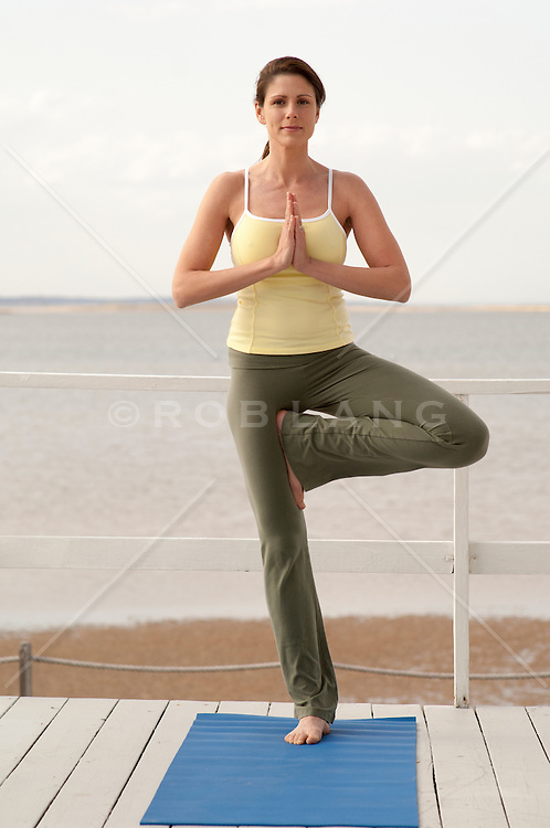 woman doing a yoga pose by the bay in The Hamptons