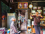 03 AUGUST 2016 - BANGKOK, THAILAND: TAWATCHAI VORAMAHAKUN, right gesturing, a community historian and leader in the Pom Mahakan slum, talks to WALLOP TANGKANA-NURAK, left, chairman of the National Legislative Assembly's (NLA) housing extraordinary committee, and other members of the NLA inside a historic home more than 150 years old during a tour of the slum. Residents of the slum have been told they must leave the fort and that their community will be torn down. The community is known for fireworks, fighting cocks and bird cages. Mahakan Fort was built in 1783 during the reign of Siamese King Rama I. It was one of 14 fortresses designed to protect Bangkok from foreign invaders. Only of two are remaining, the others have been torn down. A community developed in the fort when people started building houses and moving into it during the reign of King Rama V (1868-1910). The land was expropriated by Bangkok city government in 1992, but the people living in the fort refused to move. In 2004 courts ruled against the residents and said the city could take the land. Eviction notices have been posted in the community and people given until April 30 to leave, but most residents have refused to move. Residents think Bangkok city officials will start evictions around August 15, but there has not been any official word from the city.      PHOTO BY JACK KURTZ