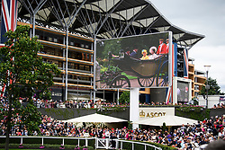 © Licensed to London News Pictures. 19/06/2018. London, UK.  A video screen shows HRH Queen Elizabeth II and Princess Anne arrive for Day one of Royal Ascot at Ascot racecourse in Berkshire, on June 19, 2018. The 5 day showcase event, which is one of the highlights of the racing calendar, has been held at the famous Berkshire course since 1711 and tradition is a hallmark of the meeting. Top hats and tails remain compulsory in parts of the course. Photo credit: Ben Cawthra/LNP