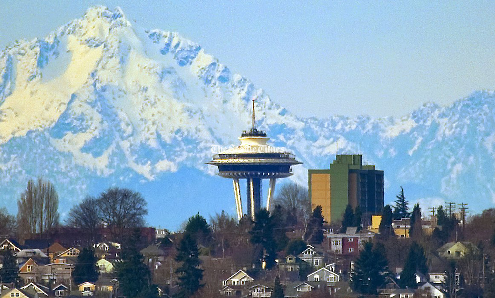 The Olympic Mountains loom behind the Space Needle in this telephoto view from Clyde Hill on the east side of Lake Washington. <br />