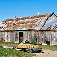 Large barn and a hay cart under a blue sky