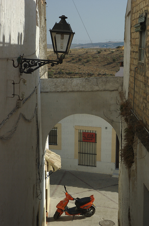 A small motorbike parked under an arch in a small Spanish town