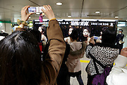 Japanese woman photographing a poster of the popular Arashi J-pop band