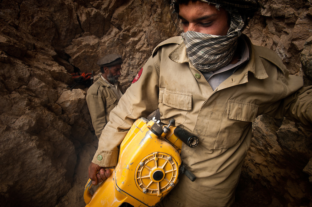 An Afghan miner carries a heavy jackhammer out of a new mine high in the mountains above the Panjshir River Valley.