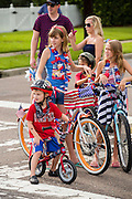 A group of children on their bicycles decorated with American flags during the Daniel Island Independence Day parade July 3, 2015 in Charleston, South Carolina.