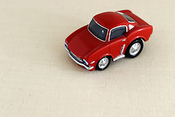 26 July 2006 a red car toy is photographed in a light tent on a fabric background.