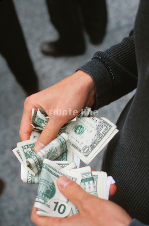 Hands fumbling with her money