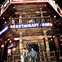 "Bar employees stand outside ""Western"" bar welcoming customers in American-style cowboy garb, Saigon, Vietnam"