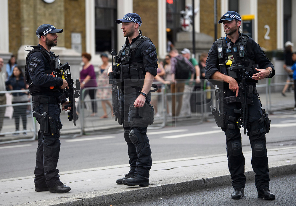 © Licensed to London News Pictures. 03/06/2018. London, UK. Heavily armed police officers watch over a minutes silence for the victims of the 2017 London Bridge Terror attack, held on London Bridge. Eight people were killed and 48 were injured when a van was deliberately driven into pedestrians on London Bridge. Three occupants then ran to the nearby Borough Market area carrying knives and fake explosives. Photo credit: Ben Cawthra/LNP