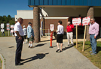 Katherine Dormody chats with Fire Chief Stephen Carrier and Fire Engineers Don Spear and Bill Akerley before casting her ballot at Gilford Middle School on Tuesday afternoon.  (Karen Bobotas/for the Laconia Daily Sun)