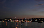 Beacon, New York - Boats are anchored in the Hudson River after sunset and before a fireworks display on July 4, 2010. Lights from the city of Newburgh are in the background. ©Tom Bushey / The Image Works
