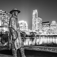 Stevie Ray Vaughan Memorial bronze statue and the Austin, Texas skyine at night black and white photo.