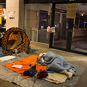 The activist volunteer medic asleep in fornt of his first aid station outside the Natwest bank in St. Paul's Square.The London Stock Exchange was attempted occypied in solidarity with Occupy Wall in Street in New York and in protest againts the economic climate, blamed by many on the banks. Police managed to keep people away fro the Patornoster Sqaure and the Stcok Exchange and thousands of protestors stayid in St. Paul's Square, outside St Paul's Cathedral. Many camped getting ready to spend the night in the square.