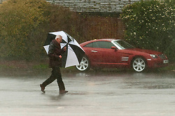 © Licensed to London News Pictures. 18/02/2020. Tewkesbury, Gloucestershire, UK. A man with umbrella rushes across a car park for cover during a downpour  at Tewkesbury in Gloucestershire. Storm Dennis continues to worsen the severe flooding at Tewkesbury in Gloucestershire, with continuing heavy rainfall in the late afternoon today. Photo credit: Graham M. Lawrence/LNP