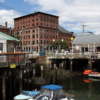 Portland, Maine waterfront with Long Wharf pier, a departure point for sightseeing cruises, on the right and the Portland Lobster Co. retaurant on the left.