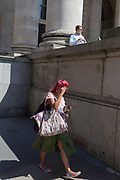 An eccentric lady with red hair walks on Threadneedle Street beneath a more conventional City worker enjoying a sunlit lunch hour at Royal Exchange Cornhill, in the City of London, the capital's ancient, financial district, on 14th May, in London, England.