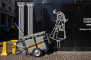 Construction hoarding woman and stationary contract street cleaning trolley.