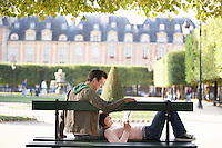 Young couple reading book sitting on bench in park