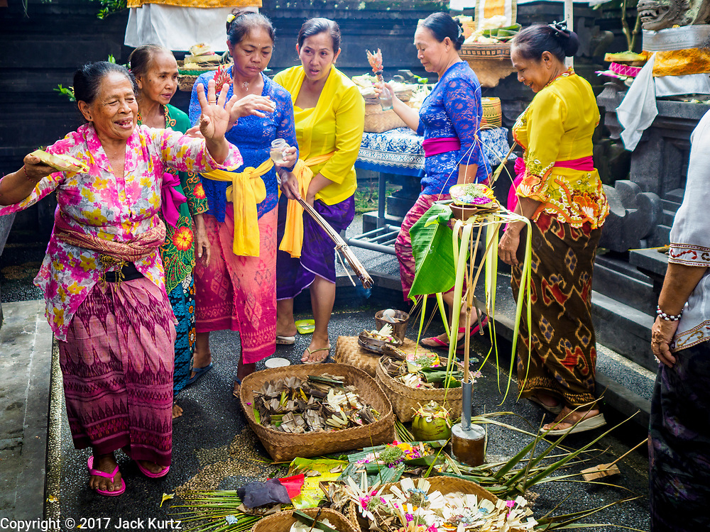 "08 AUGUST 2017 - UBUD, BALI, INDONESIA: Women dance during a ceremony to honor a family temple in Ubud, Bali. Balinese Hindus have a 210 day calender and every almost every family compound on Bali has a family temple. Once a year (or every 210 days) families celebrate the ""birthday"" of their temple with a ceremony.     PHOTO BY JACK KURTZ"