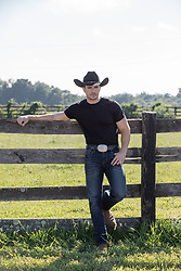 hot cowboy leaning against a wooden fence
