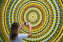 "© Licensed to London News Pictures. 19/09/2019. London, UK. A member of the gallery staff takes a photograph of Damien Hirst's butterflies and household gloss canvas titled ""Cardinal"" on her phone.<br />