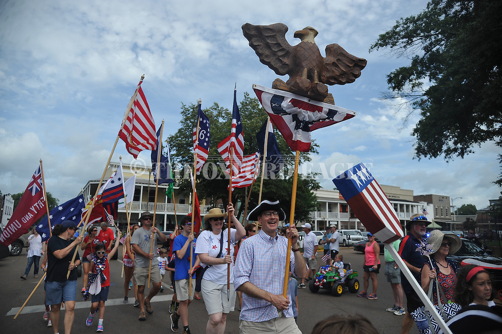 Jason Bouldin, right, carries an eagle as he leads those carrying Revolutionary War era flags during a 4th of July parade in Oxford, Miss. on Monday, July 4, 2016. (Bruce Newman, Oxford Eagle via AP)