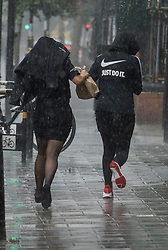 © Licensed to London News Pictures. 11/07/2017. London, UK. Two women run for cover as a sudden burst of heavy rain catches people out in central London. Photo credit: Peter Macdiarmid/LNP