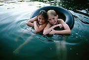 NJ, Morris County, Northeast, Young girls in inner tube on pond