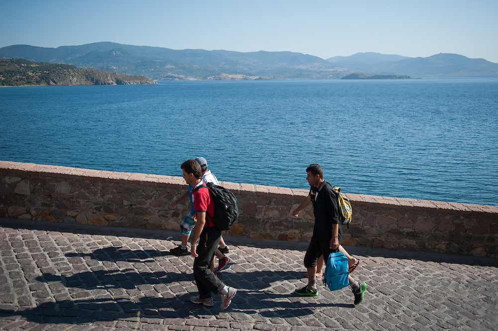 Syrian refugees walk from the port of Molyvos to a car park that a Coast Guard's bus waits to take them to one of the camps in Mytiline