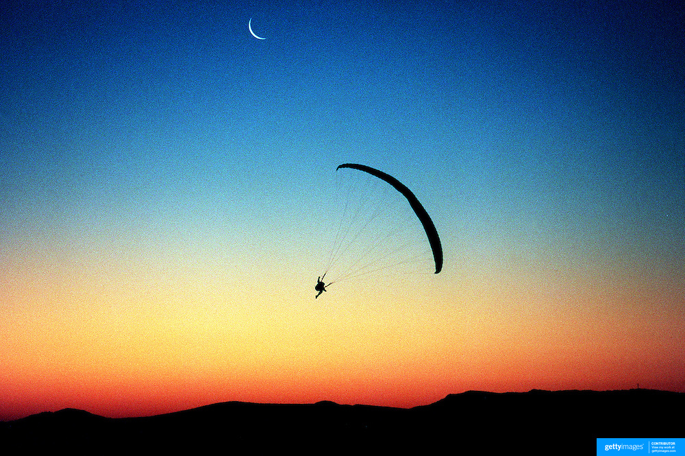 A paraglider in action during sunset as a new moon appears over Mount Borah, Manilla near Tamworth, NSW, Australia before competition in the Australian Paragliding Championships.