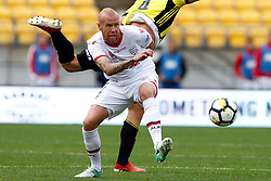 Adelaide United's Taylor Regan, left, looks towards the ball as the Phoenix's Goran Paracki recovers his balance in the A-League football match at Westpac Stadium, Wellington, New Zealand, Sunday, October 08, 2017. Credit:SNPA / Dean Pemberton **NO ARCHIVING**