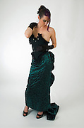 woman aged 30 in green evening dress and black gloves, on white background full body frontal view model looking down. Model Released