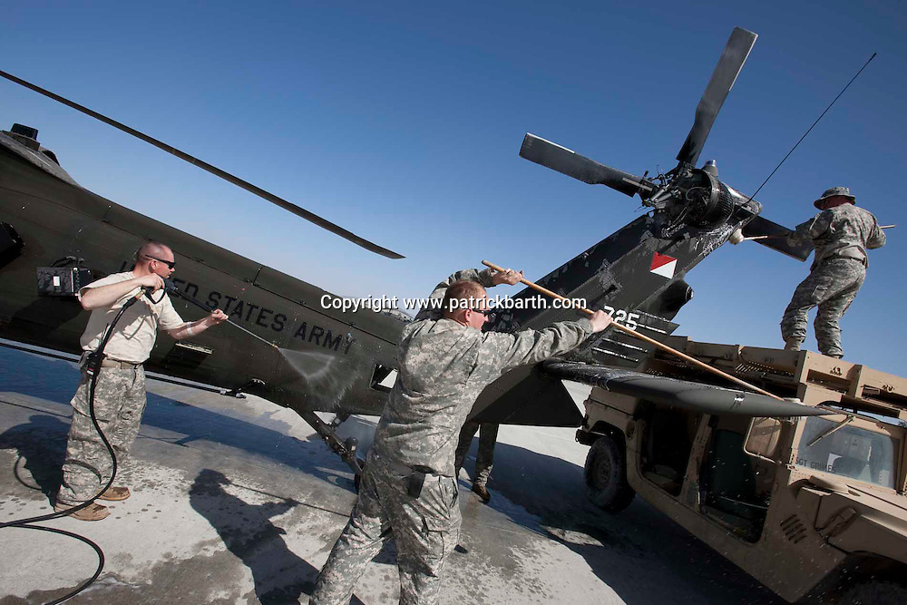 "Jalalabad, Eastern Afghanistan: As part of the 120 hour service the maintenance crew gives the ""bird"" a good wash. Maintenance is vital for Blackhawk helicopters. For every hour in the air there between three and four hours on the ground are spent on maintenance."