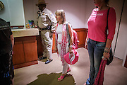 """31 JULY 2012 - PHOENIX, AZ:  MEDEA BENJAMIN, center, and other members of Code Pink, accompanied by an Arizona State Trooper, wait in the lobby of the governor's office at the Arizona State Capitol Tuesday. Medea is a political activist, best known for co-founding Code Pink and, along with her husband, activist and author Kevin Danaher, the fair trade advocacy group Global Exchange. She was also a Green Party candidate in 2000 for the United States Senate. She appeared in Phoenix to promote her new book, """"Drone Warfare: Killing by Remote Control."""" She, and other members of Code Pink, presented a letter to Arizona Gov. Jan Brewer protesting Brewer's request to use the state's airspace to train drone pilots.  PHOTO BY JACK KURTZ"""