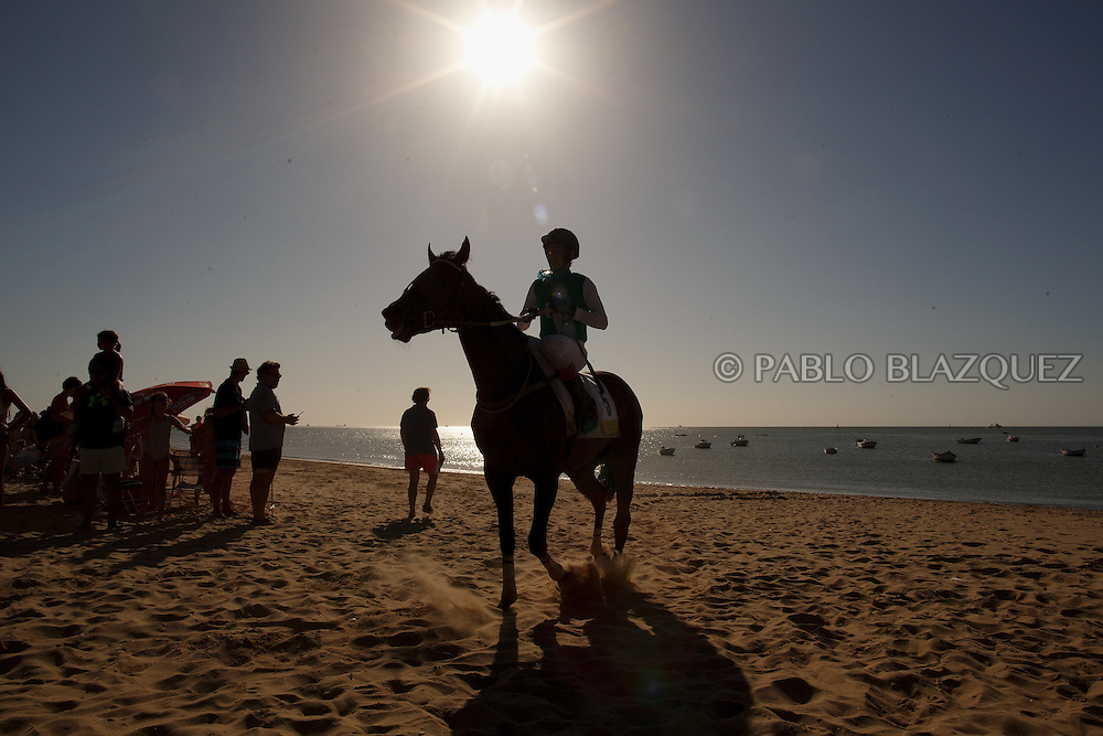 12/08/2016. A jockey rides his horse along the beach after racing during the beach horse races on August 12, 2016 in Sanlucar de Barrameda, Cadiz province, Spain. Sanlucar de Barrameda yearly horse races traditional origin started with informal races of horse's owners delivering fish from the port to the markets. But the first formal races date back to 1845 and they are the second oldest in Spain, after Madrid. The horse races take place near the Guadalquivir river mouth during August